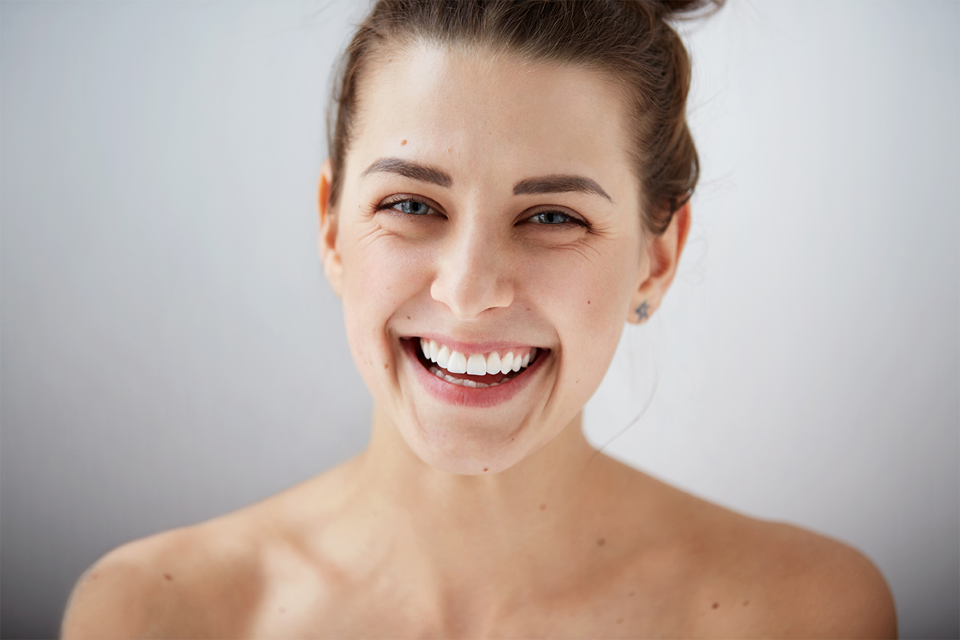 Beauty girl face Portrait. Beautiful model woman perfect fresh clean skin. Female looking at camera and smiling. Youth and skin care concept. Isolated on background